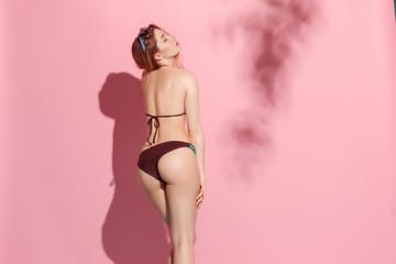 Beautiful female model posing on pink background