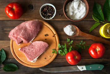 Raw pork meat and ingredients on a wooden board.