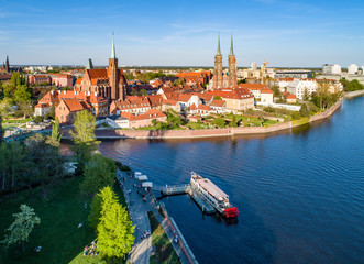 Poland. Wroclaw. Ostrow Tumski, Gothic cathedral of St. John the Baptist,  Collegiate Church of the Holy Cross, Archbishop's palace, tourist harbor, ship and Odra (Oder) River. Aerial view at sunset
