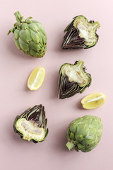 Overhead view of fresh artichokes over pink background