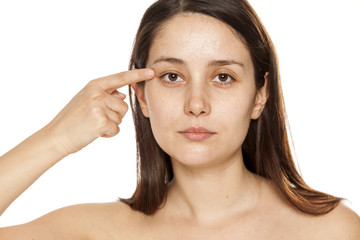Young woman pointing on her eye on white background