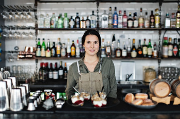 Portrait of woman standing behind bar