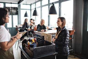 Owner talking to smiling young customer while standing in lectern