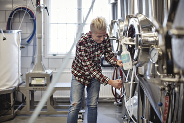 Female manager working by storage tank at brewery