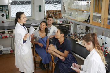 Happy mature teacher explaining to young multi-ethnic university students sitting in chemistry laboratory