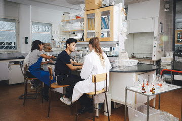 Multi-ethnic young university students sitting on chairs in chemistry laboratory