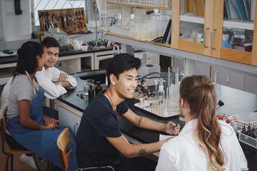 High angle view of multi-ethnic young university students sitting on chairs in chemistry laboratory