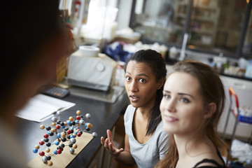 Young female students by molecular structure looking at mature teacher in chemistry classroom