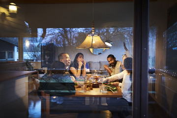 Multi-generation family talking while having dinner at table seen through window