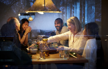 Happy family enjoying while having dinner at table seen through glass window