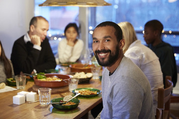 Portrait of smiling father sitting with family during meal at table