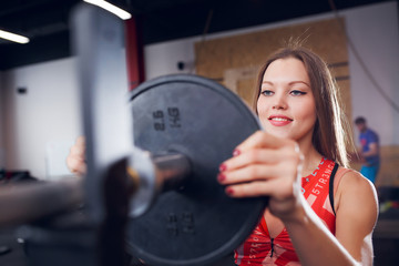 Picture of smiling sportswoman in sports clothes with barbell