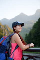 Image of tourist brunette with backpack on background of picturesque mountains