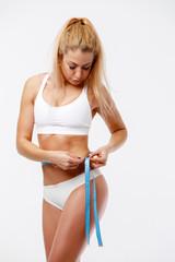 Image of slender blonde measuring waist with centimeter ribbon in studio
