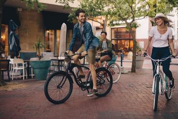 Friends enjoying riding bicycles on city street