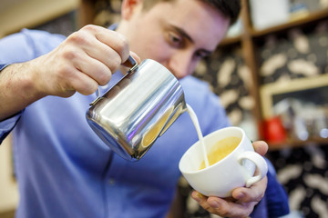 Photo of barista man pouring milk into cup of coffee