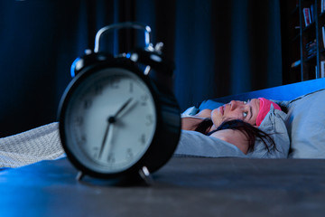 Photo of woman with insomnia with pink eye bandage lying on bed next to alarm clock