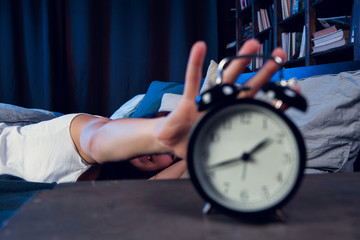 Image of dissatisfied brunette with insomnia stretching arm to alarm clock at night