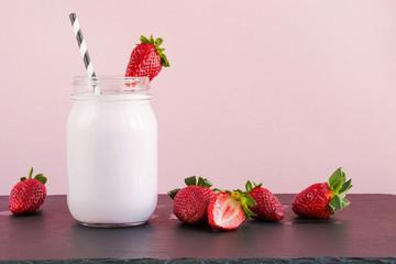 Strawberry milkshake with berry in mason jar on pink. Close up. Summer drink.