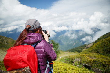 Image of photographer girl with backpack backdrop of mountains