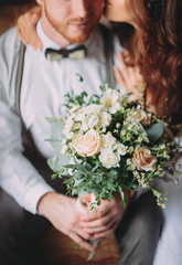 stylish groom with beard and beautiful bride posing in hotel