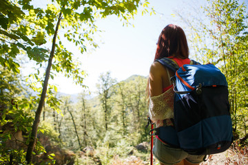 Image from back of young woman with sticks for sporty walk