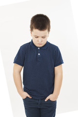 Angry little boy with hand in pockets. Isolated on white background