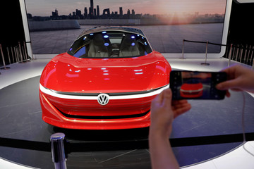 A visitor takes pictures of Volkswagen's I.D. Vizzion model car displayed during a media preview of the Auto China 2018 motor show in Beijing