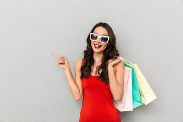 Pleased brunette woman in casual clothes and sunglasses holding packages