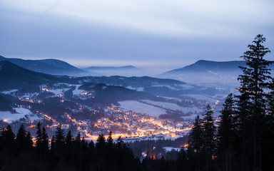 Night beautiful scene of winter landscape of shining village surrounded by mountains and deep spruce tree forest in fog during twilight. Creative long exposure photography with headlight motion blur.
