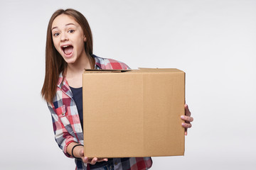 Delivery, relocation and unpacking. Excited young woman holding cardboard box, looking at camera, surprised, isolated