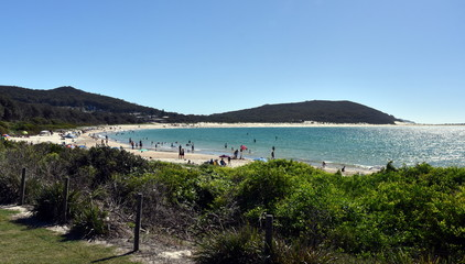 """Fingal Bay on a sunny day in autumn time (NSW Australia). People relaxing and sun bathing on the beach.The bay was originally known as """"False Bay""""."""