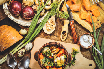 preparation of spring dish dandelions with pumpkin and mushrooms. ingredients and spices. wooden background.
