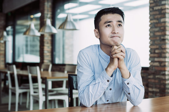 Closeup portrait of young Asian man looking up, praying with his hands clasped and sitting at empty table with blurred cafe interior in background