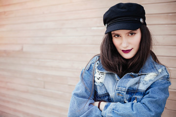 Fashion close up  portrait of amazing woman with bright make up and trendy outfit, wearing jeans coat and trendy black hat,cap toned colors.Copy space, urban wall background.