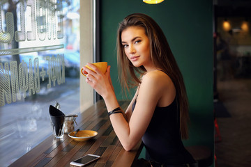 Young female brunette model in cafe