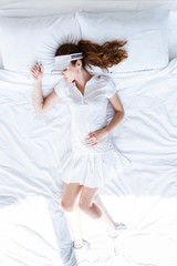 Top view of redhead girl in tennis clothes sleeping on bed