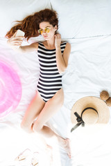 Top view of girl in swimsuit taking selfie on bed among travel objects