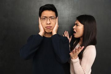 Displeased asian man in eyeglasses covering ears
