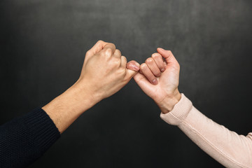 Cropped image of Asian couple holding pinkies to each other