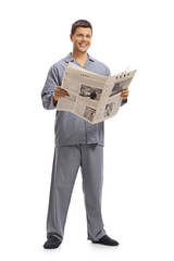 Young man in pajamas holding a newspaper
