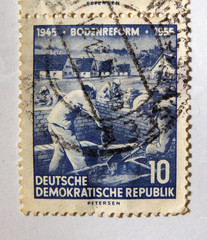 Leeds, England - April 18 2018: An old blue east german postage stamp with building workers on a construction site