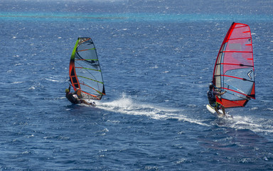two windsurfers on sailboards are moving at a speed along the sea surface
