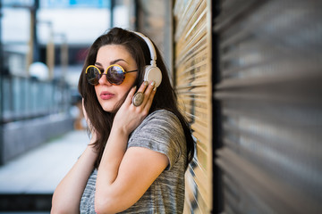 Young woman Listening to the music at the street on a headphones