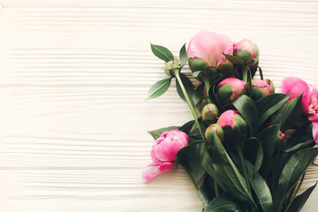 lovely pink peonies on rustic white wooden background top view, space for text. floral greeting card, flat lay. beautiful peony flowers pattern, tender image. happy mothers  day concept