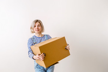 Photo of woman with cardboard box in new empty apartment