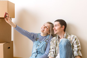 Photo of young married couple doing selfie sitting on floor among cardboard boxes