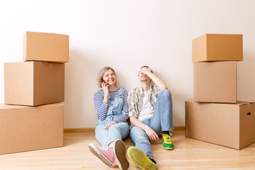 Image of young married couple sitting on floor among cardboard boxes