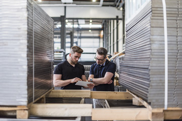 Two men using tablet in factory