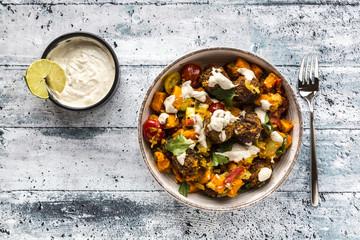 Vegetarian bowl with sweet potato, tomato and falafel, yogurt dip and parsley